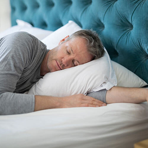 Middle-aged man sleeping peacefully on his side